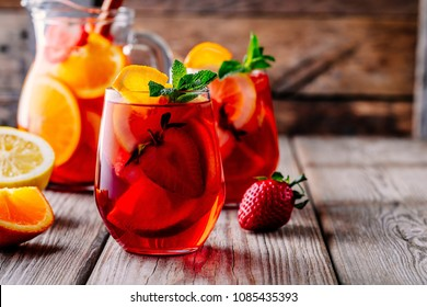 Homemade red wine sangria with orange, apple, strawberry and ice in glass and pitcher on rustic wooden background