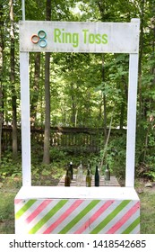 Homemade ring toss booth kids carnival game painted mostly white with bright greens & pink. Looking though to a wooden pallet with a number of empty bottles set up for the game and a forest backdrop.