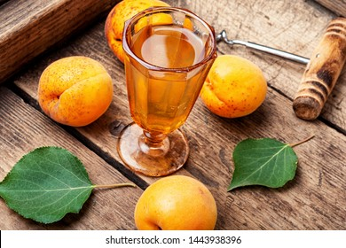 Homemade ripe apricot wine.Alcoholic drink.Fruit wine on wooden table