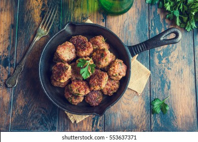 Homemade roasted beef meatballs in cast-iron skillet on wooden table in kitchen, fresh parsley, vintage fork, top view.
