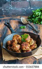 Homemade roasted beef meatballs in cast-iron pan on wooden table in kitchen.