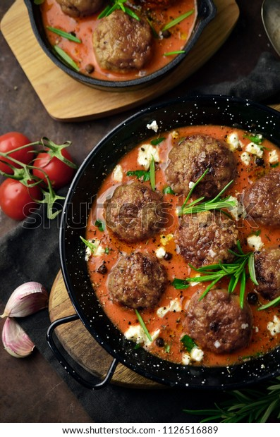 Homemade roasted beef meatballs in cast-iron skillet on wooden table
