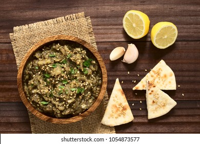 Homemade roasted eggplant dip or spread, baba ganoush in the Mediterranean cuisine, with olive oil, sesame, parsley on top, sesame pita chips on the side, photographed overhead with natural light