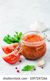 Homemade roasted garlic marinara tomato sauce in glass jar on concrete background. Selective focus, space for text.