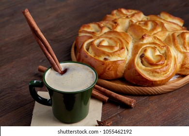 Homemade rose bread, cup of coffee, anise and cinnamon on vintage background, close-up, selective focus