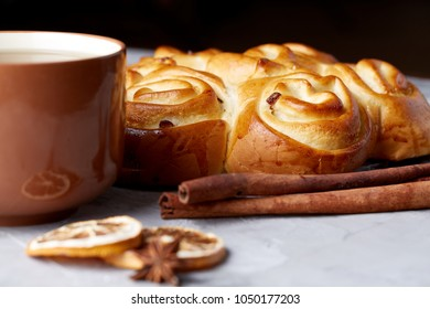 Homemade rose bread, cup of tea, dried citrus and spicies on white textured background, close-up, shallow depth of field