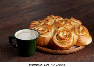 Homemade rose bread on wooden tray with cup of coffee on vintage background, close-up, selective focus