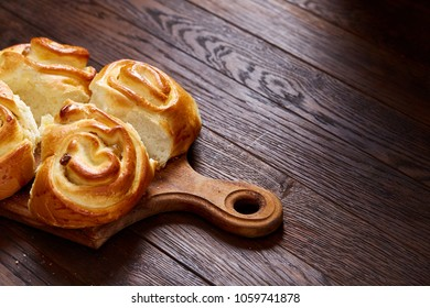 Homemade rose buns on wooden cutting board over rustic vintage background, close-up, shallow depth of field