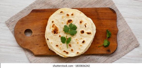 Homemade Roti Chapati Flatbread on a rustic wooden board, top view. Overhead, from above, flat lay.