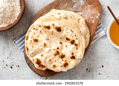 Homemade Roti Chapati Flatbread on gray concrete background top view. Freshly baked indian flatbread