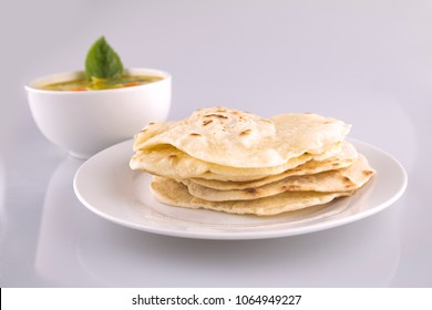 Homemade Roti with green curry on the back. Indian Food at home. Roti or Chapati on white background.