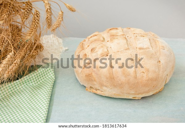 Homemade round bread, ears of wheat and flour