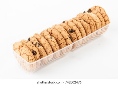 Homemade round ginger biscuit with peanuts and raisins. Delicious honey sweetmeal digestive cookie in a plastic box. On a white background with light shadow. Detailed closeup studio shot.