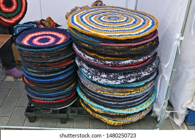 Homemade round knitted rugs that are placed near the door are sold on the street. Snapshot style image
