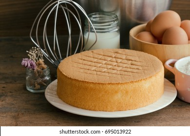 Homemade round sponge cake or chiffon cake on white plate so soft and delicious with ingredients: eggs flour milk on wood table in side view. Homemade bakery concept for background and wallpaper.