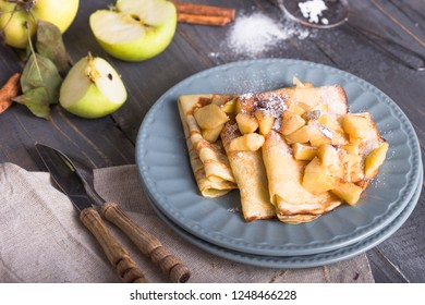 Homemade Russian crepes for breakfast  and fresh apples on wooden blue background top view
