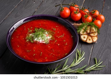 Homemade Russian, Ukrainian and Polish national soup - red borscht made of beetrot, vegetables and meat with sour cream on a gray wooden background