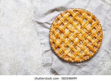 Homemade rustic apple pie preparation greased with egg yolk on white kitchen background. Flat lay. Copy space.