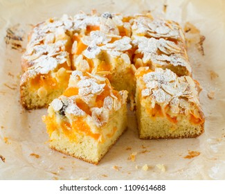 Homemade rustic apricot cake with almonds on parchment paper