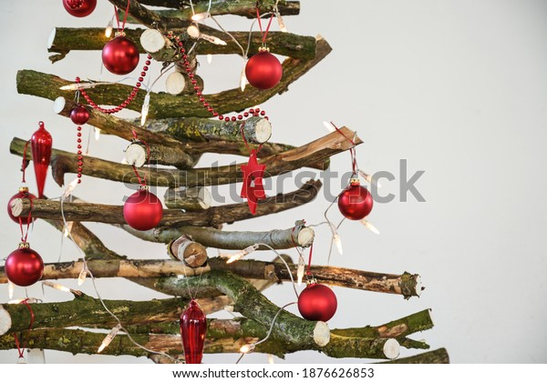 Homemade rustic Christmas tree made of raw wood branches  with fairy lights and red balls, sustainable and environmentally friendly alternative for the holidays, selected focus, narrow depth of field