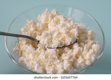 Homemade rustic crumbly cottage cheese on a blue background.