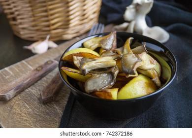 Homemade rustic food: potatoes with mushrooms closeup. vertical top view