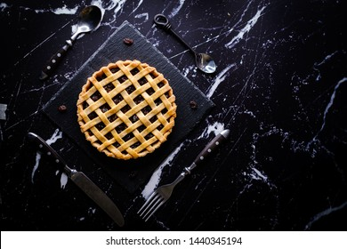 Homemade rustic pastry Traditional Raisin Pie tart cake. Set on on a dark modern marble background.
