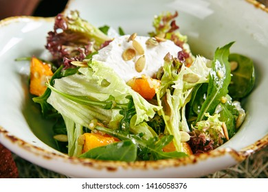 Homemade Rustic Salad with Baked Pumpkin and Cheese Mousse on Hay Background Close Up. Macro Photo of Simple Peasant Salat with Fresh Green Lettuce Leaves Decorated with Pumpkin Seeds