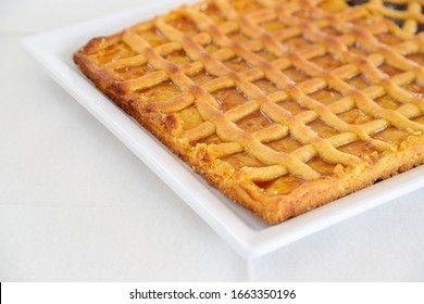 Homemade rustic tart with apricot jam. Italian dessert. White background and copyspace