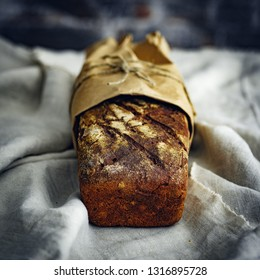 Homemade rye bread in the kraft paper on linen tablecloths