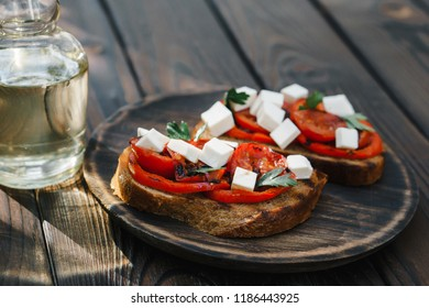 Homemade rye bruschetta with grilled tomatoes and feta cheese, tasty healthy snack close up