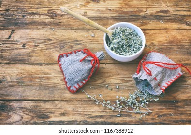 homemade sachets with wormwood, white bowl with dry herbs on wooden table, top view