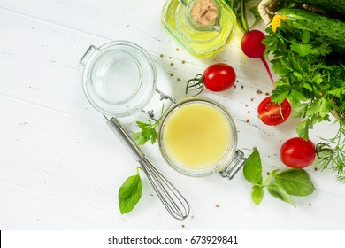 Homemade salad dressing vinaigrette with mustard and olive oil on a white kitchen wooden table. Top view with copy space.