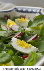 Homemade salad from fresh leaves of lettuce, arugula, radish and boiled eggs in a ceramic plate on white wooden background. Close up. Traditional polish pottery from Boleslawiec.