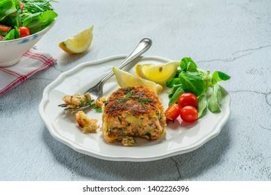 Homemade salmon fish cake with fresh leaf salad garnished with lemon