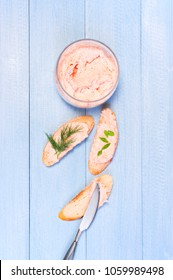 Homemade salmon pate in the glass jar on blue wooden table, top view