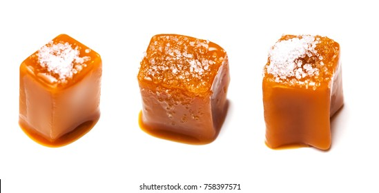 Homemade salted caramel pieces isolated on white background. Golden Butterscotch toffee candy caramels macro.