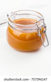 Homemade salted caramel sauce in a glass jar on stone table