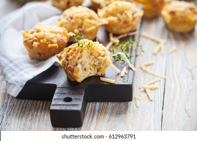 Homemade salted muffin with ham and cheese on a wooden serving board
