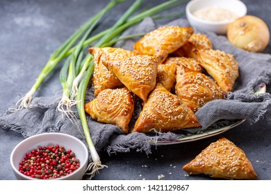 Homemade samosas with meat on a plate, sesame, onion and pepper on a dark textured background, selective focus.