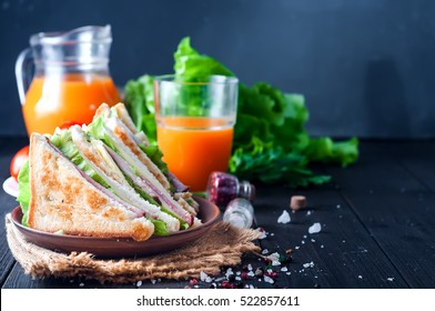 homemade sandwich with salad and juice as a healthy breakfast on a dark background. Space for text