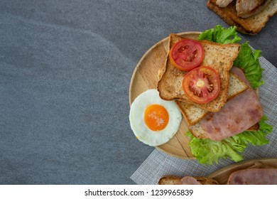 Homemade sandwich or toast wheat bread with fried egg,lettuce,tomato in wooden table on the concrete table.