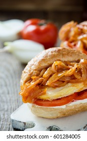 Homemade sandwiches with fried chicken breast and sweet onion sauce on rustic wooden table
