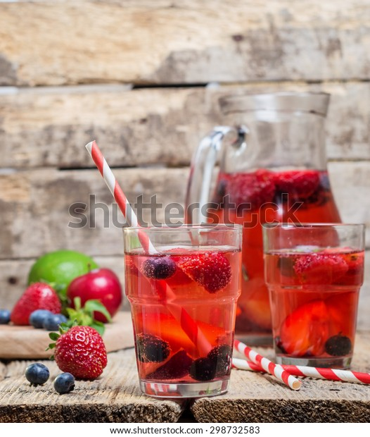 homemade sangria with fresh berries, fruit and lime on wooden rustic table