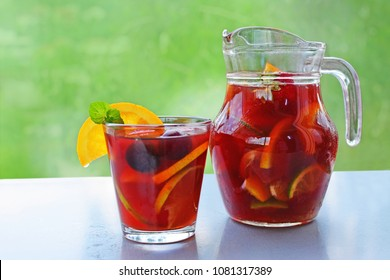 Homemade Sangria refreshing fruit punch beverage in pitcher and glass over an outdoor table