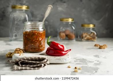 Homemade sauce adjika with hot pepper, garlic, basil, parsley and walnuts. Tabasco
