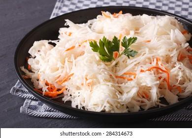 homemade sauerkraut with carrot in a black plate close-up horizontal