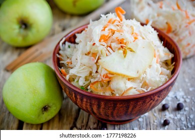 Homemade sauerkraut with green apple and carrot in a clay bowl