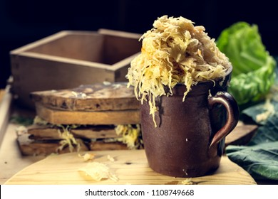 Homemade sauerkraut pickling. Pulling sauerkraut from the barrel with a ceramic jug. In the background of oak planks pulled out of the barrel.