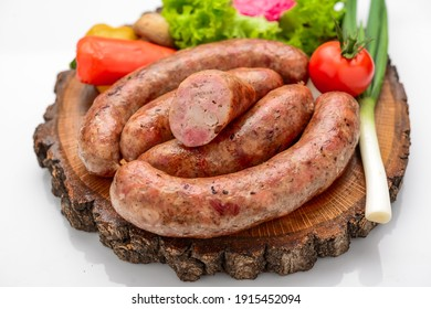Home-made sausage with vegetables on a wooden board